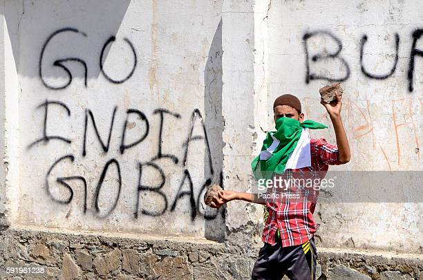 A young Kashmiri protester gestures near a wall painted with antiIndia graffiti's during an antiIndia and proKashmir protest rally after Friday...