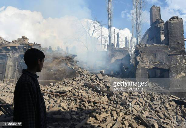 TOPSHOT A young Kashmiri villager looks at the remains of a house destroyed during a deadly gun battle between militants and Indian government forces...
