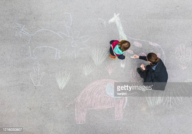 young kid and his mother drawing on asphalt with chalk - chalk art equipment stock pictures, royalty-free photos & images