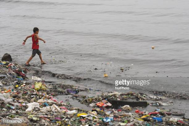 A young kid collects a ball in the Pasig River out of a costal road in Baseco Compound in Manila The Batangas Shipping and Engineering Company...
