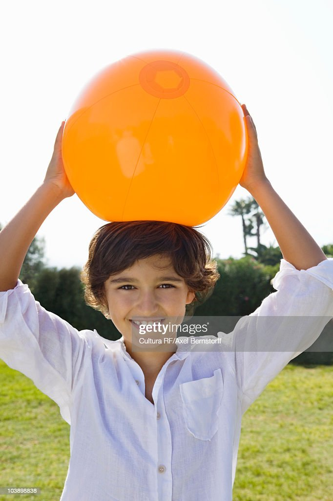 Young kid holds an orange ball over head : Stock Photo