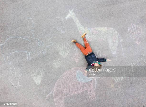 young kid lying down on the asphalt colored with chalk - chalk art equipment stock pictures, royalty-free photos & images