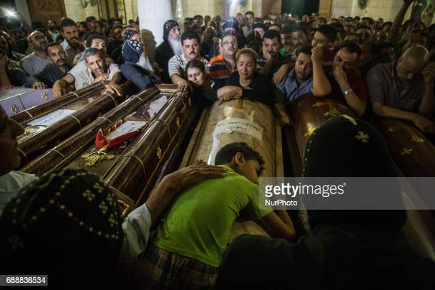 A young kid next to the coffins of his parents who were killed during a bus attack during their funeral service at Ava Samuel desert monastery in...