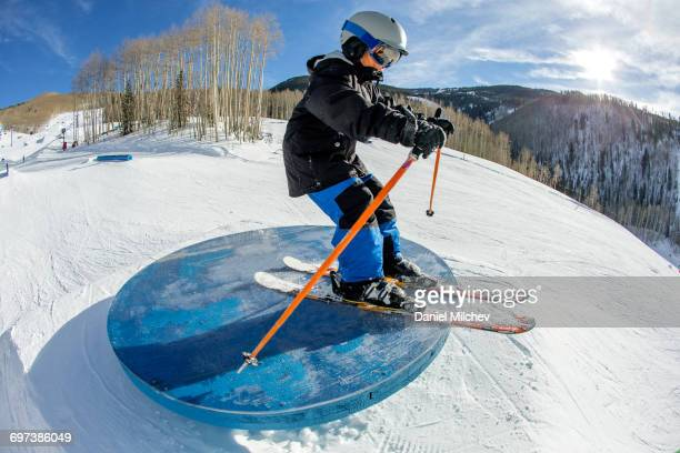 Young kid skiing on a table top in a terrain park.