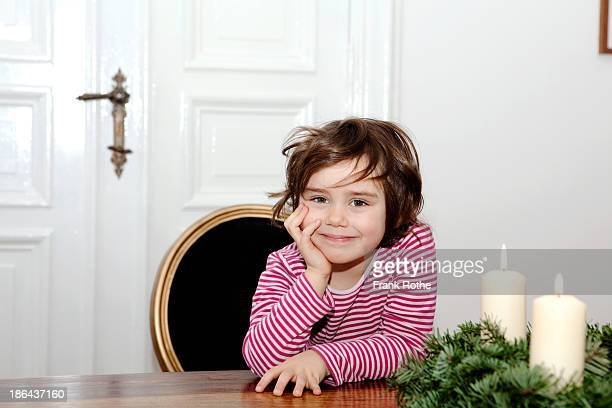 young kid smiling while sitting beside candles