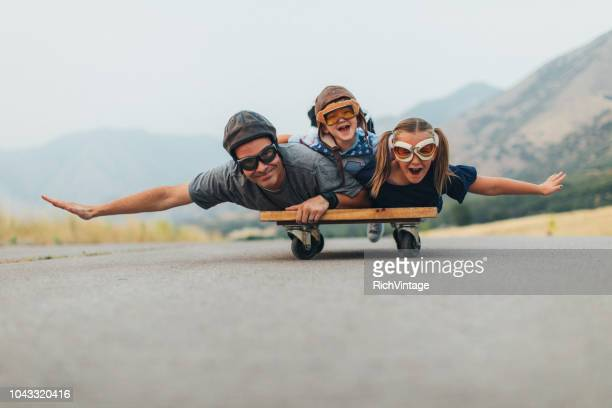 young kids and dad flying on a press cart - pai imagens e fotografias de stock