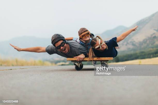 young kids and dad flying on a press cart - saturday stock pictures, royalty-free photos & images