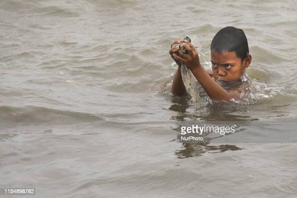 Young kids fishes shellfish collected on the beach in Manila Bay near Baseco Compound The Batangas Shipping and Engineering Company Compound is the...