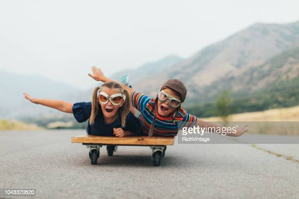 young kids flying on a press cart - arms outstretched stock pictures, royalty-free photos & images