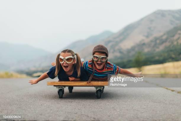 jeunes enfants voler sur un chariot de presse - insouciance photos et images de collection