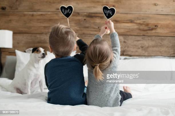 young kids happy childrens family playing in the parent's bed with their for - love you stock photos and pictures