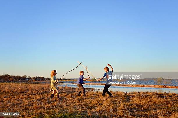 young kids playing with sticks . - lynn pleasant stock pictures, royalty-free photos & images