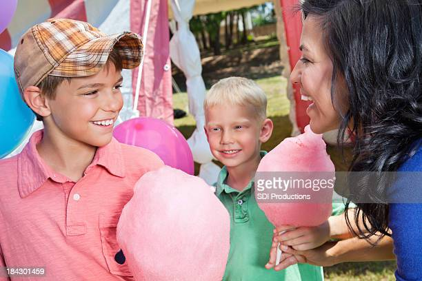 Young Kids Receiving Cotton Candy From Mom at Carnival