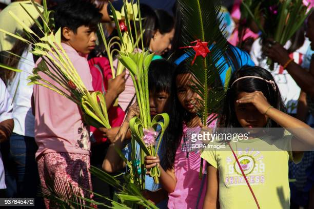 CHURCH ANTIPOLO RIZAL PHILIPPINES Young kids sell palm fronds outside the Antipolo church in Antipolo city east of Manila Catholic devotees mark the...