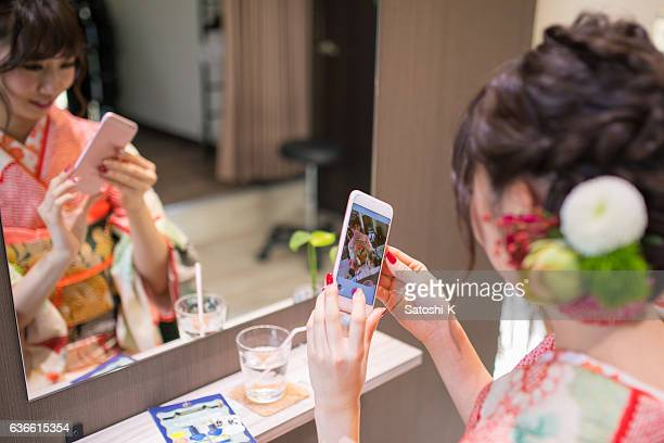 Young kimono girl taking selfie picture in beauty salon