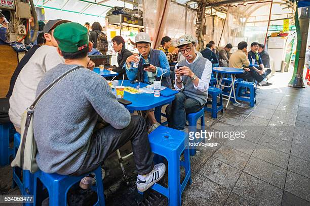young korean hipsters on cellphones in street cafe seoul korea - korean food stock pictures, royalty-free photos & images
