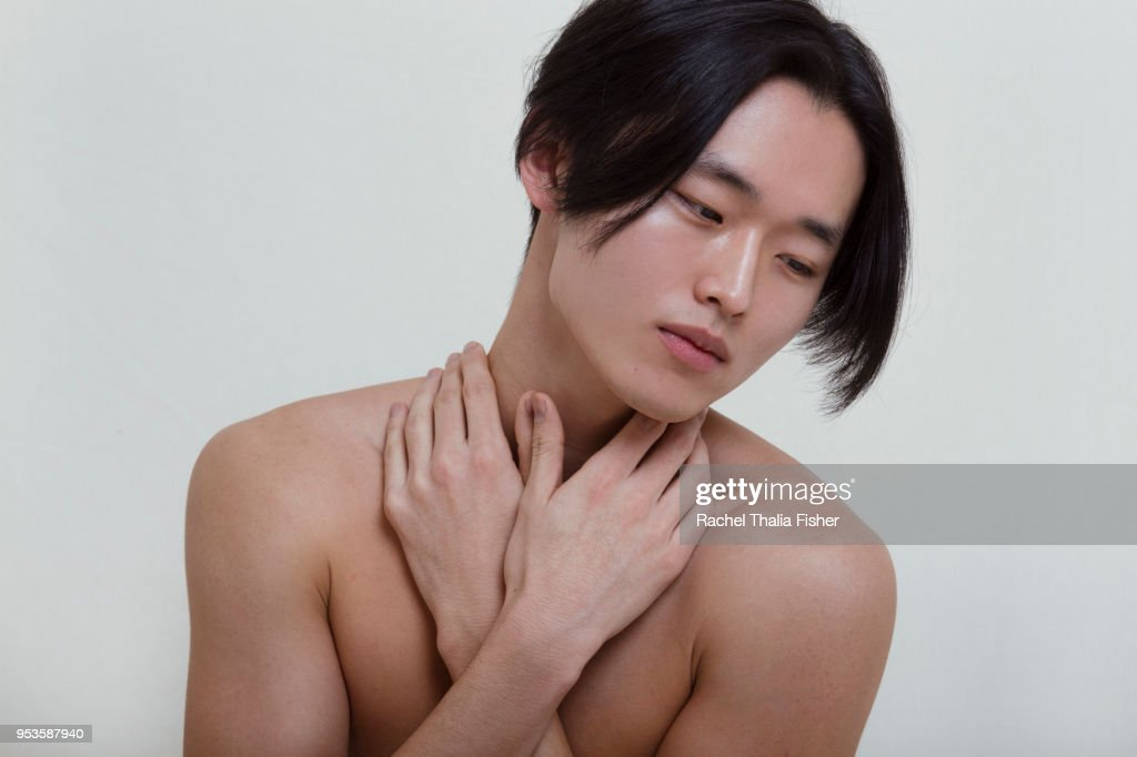 Young Korean male adult with hands crossed looking introspective : Stock Photo