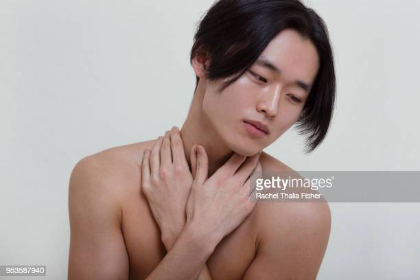 Young Korean male adult with hands crossed looking introspective