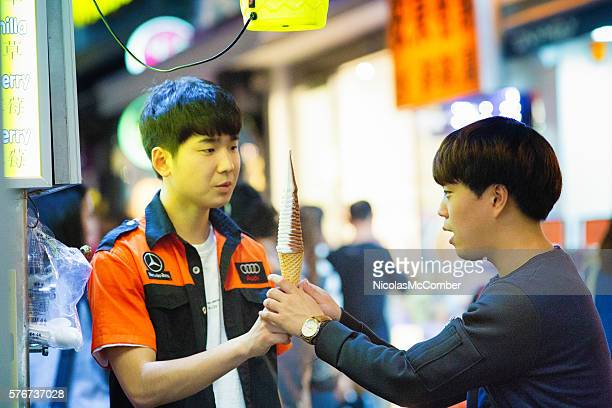 Young Korean street stand worker handing soft ice cream cone