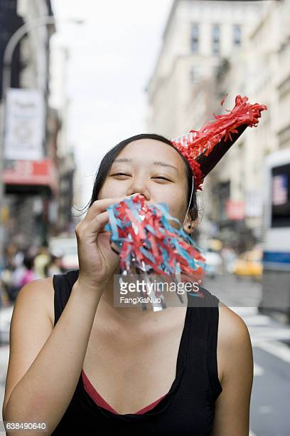 young korean woman blowing party horn in downtown city - new yorker building stock photos and pictures