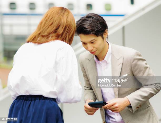 young korean worker bows to female japanese colleague - humility stock pictures, royalty-free photos & images