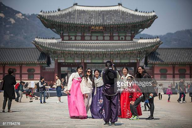 Young Koreans wearing hanbok take snapshots with foreign visitors inside Gyeongbok Palace on March 27 2016 in Seoul South Korea There has been a...