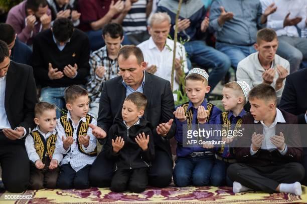 Young Kosovo Muslims attend the Eid alFitr prayer near the Sulltan Mehmet Fatih mosque in Pristina on June 25 2017 Eid alFitr festival marks the end...