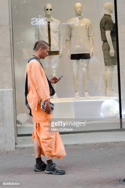 young krishna man dressed in peached robe and texting downtown budapest during summer day - krishna stock photos and pictures
