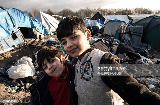 Young Kurdish boys from Iraq pose in a migrant and refugee camp in GrandeSynthe near Dunkirk northern France on January 12 2016 Around 3000 refugees...
