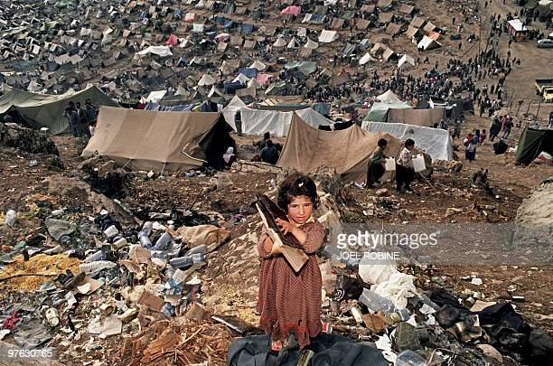 A young Kurdish girl holds a US Army rations 05 May 1991 as the tents of the Cukurca refugee camp on the Turkish side of the Iraqi border are seen in...