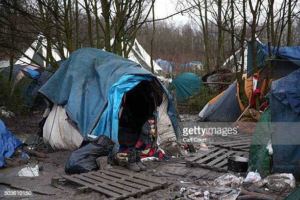 A young Kurdish girl looks out from a tent in a new migrant camp on January 6 2016 in Dunkirk France Thousands of migrants continue to live in...