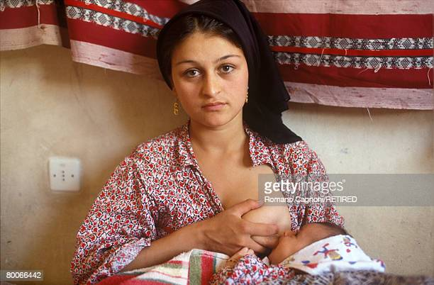 A young Kurdish refugee breastfeeds her baby in the Turkish region of Kurdistan circa 1990