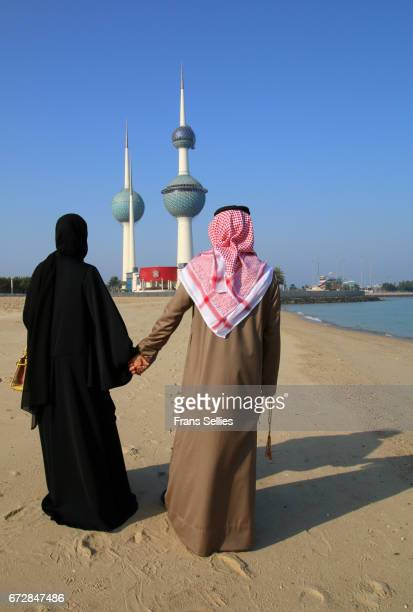 young kuwaiti couple walking hand in hand on the beach, kuwait city - frans sellies stockfoto's en -beelden