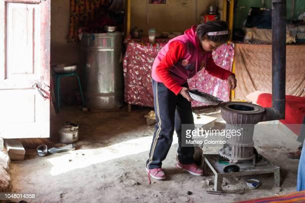 young kyrgyz girl inside a yurt near the stove - pobreza questão social - fotografias e filmes do acervo