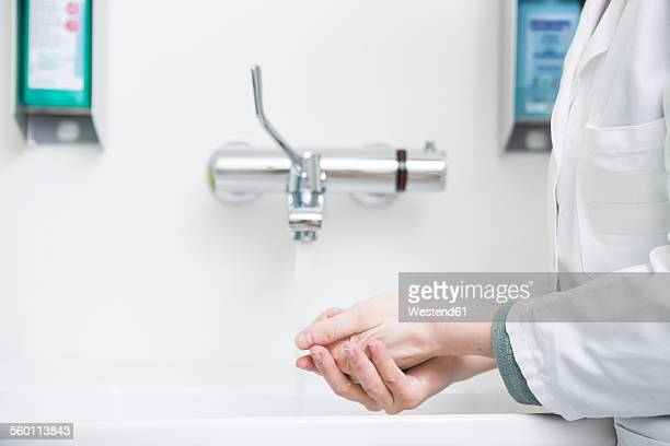 Young lab technician washing hands
