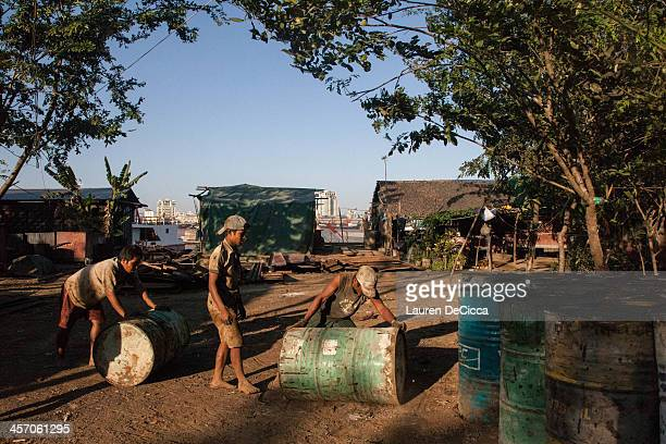 Young laborers stacks recycled oil drums weighing 240kg on the banks of the Irrawaddy River in the Dala township of Yangon on December 16 2013 in...