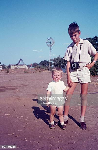 Young lad of 10 poses for a portrait taken by his brother while holding the hand of his young nephew. Confusingly, the 10 year-old uncle and the 1...