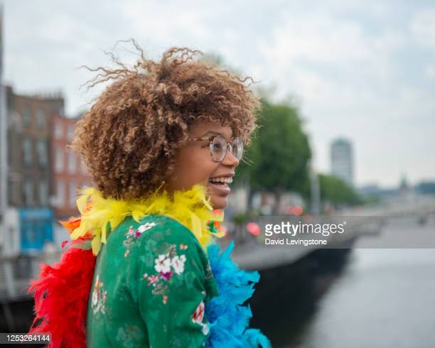 young lad with gay pride feather boa in support of lgbtqi - street stock pictures, royalty-free photos & images