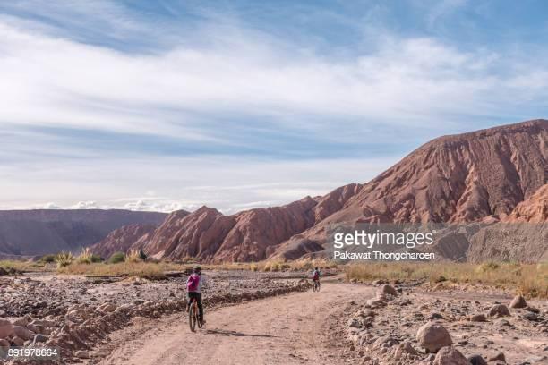 young ladies biking to quebrada del diablo, san pedro de atacama, chile - antofagasta region stock photos and pictures