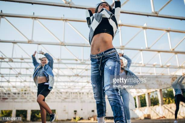 young ladies dancing together on the street - south_agency stock pictures, royalty-free photos & images