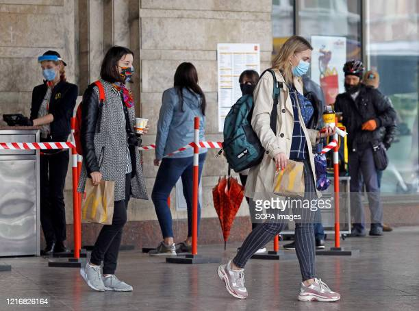 Young ladies wearing face masks as a preventive measure against the spread of coronavirus are seen leaving McDonald's restaurant with their food...