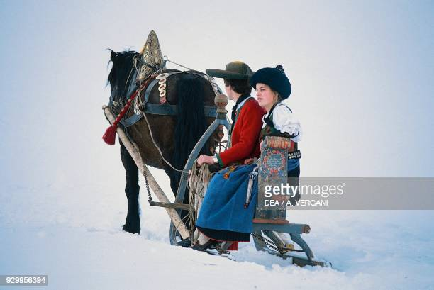Young Ladin people wearing traditional clothes on a horsedrawn sleigh snowy landscape Val Badia TrentinoAlto Adige Italy