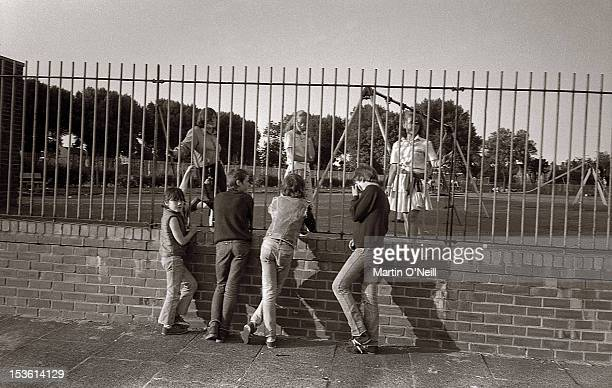 Young lads chat to young girls through the bars of 'Patty Rec' Patricroft Recreation Ground in Eccles Greater Manchester