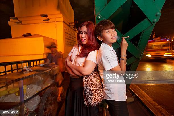 A young lady and her tomboy partner pose on a bridge together over a river in Bangkok city Tomboys often seek to fit into the community and are...