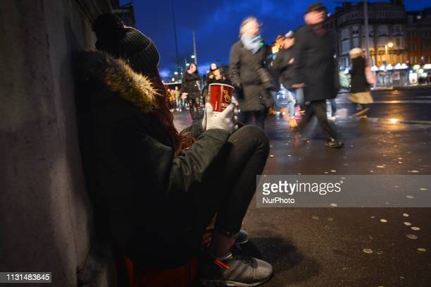 A young lady begging at Dublin's O'Connel bridge just before St Patrick's Day On Saturday March 16 in Dublin Ireland