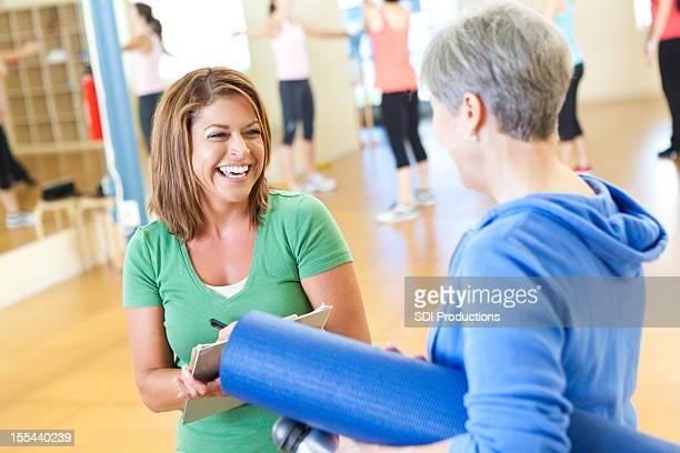 Young lady comprobación de mujer madura en clase de ejercicio
