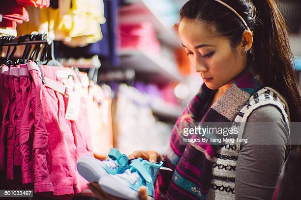 Young lady choosing shoes in department store