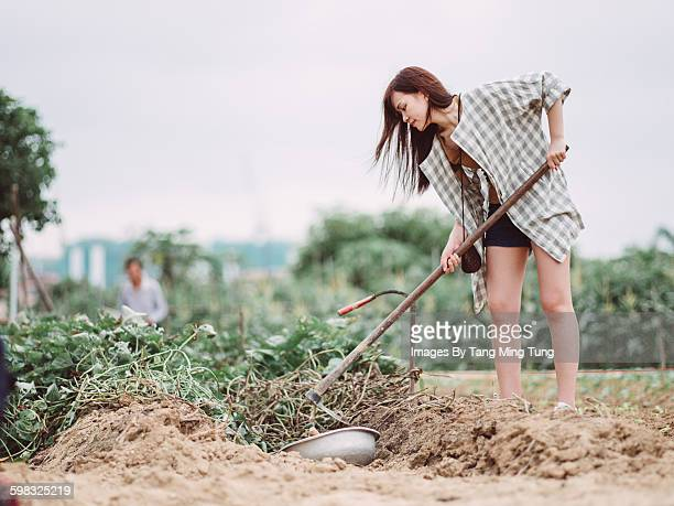 Young lady digging soil with hoe in field