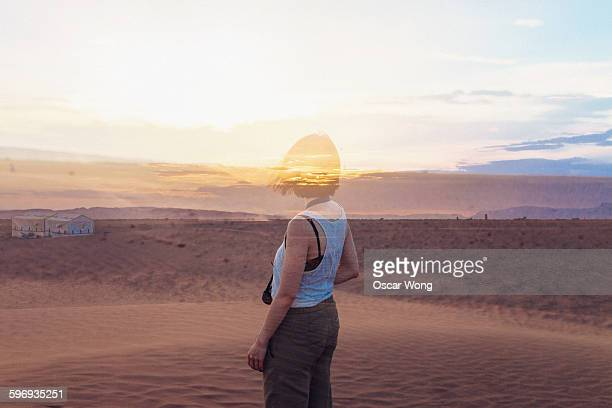 Young lady disappearing in desert landscape