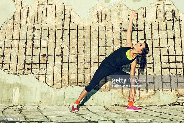 young lady doing stretches outdoors by concrete - harriet stock photos and pictures